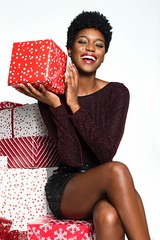 Photo of smiling woman with her eyes closed sitting on gift - Credit to https://homegets.com/