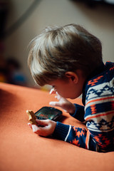 Closeup of young boy playing videogames on mobile phone