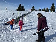 The twins at the bunny lift at Les Houches as Kate brings their skis