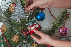 Women's hands hang a toy car on the Christmas tree