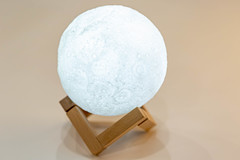 Night light in the form of a shining moon on a wooden stand