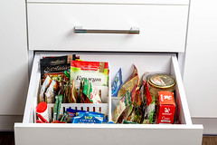Open kitchen drawer with various spices