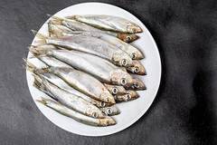 A plate of raw fish on a black background. Top view