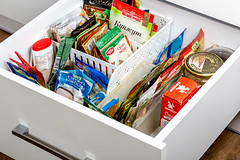 Side view of a spices and groceries organized in a white kitchen drawer