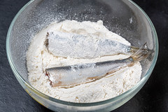 Glass bowl with flour and raw fish