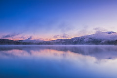 Sapphire lake amid autumnal mountains