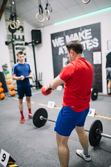 Personal trainer helping his client to lift weight in a gym