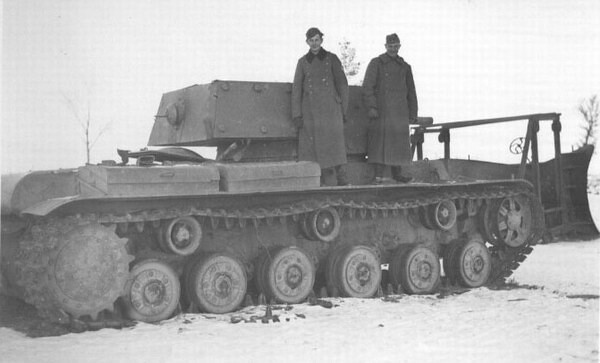 gruene-teufel: German soldiers pose atop a captured KV-1E heavy tank, on the front of which has a makeshift snow plow mounted, probably in the Winter of 1941-1942.