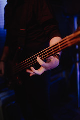 Hand performing on a Bass. Professional bass player live.
