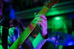 Guitarist Performing Live. Arm on guitar neck closeup