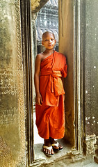 Young Buddhist monk posing inside the Angkor Wat in Cambodia