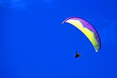Paraglider flying freely against clear blue sky