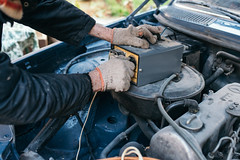 Auto mechanic checking old car battery voltage