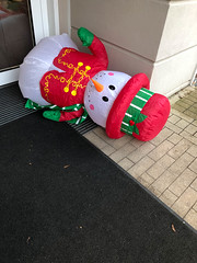 Christmas time is over: Snowman lies on the floor outside the house