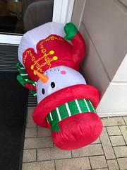 Aufblasbarer Schneemann liegt auf dem Boden vor der Haustür