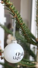 """Weiße Weihnachtsbaumkugel mit der Aufschrift """"O holy Night"""" hängt an einem grünen Zweig"""