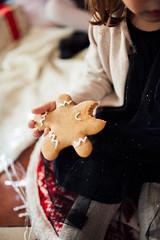 Little girl eating gingerbread.