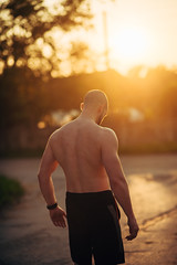 Musculine man posing at sunset on street