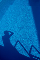 A mans shadow in the water of the pool