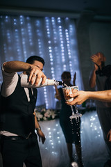 Groom pouring chapagne into glasses with a hand holding them