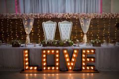 Wedding chairs set for couple with a big sign saying love with romantic lights