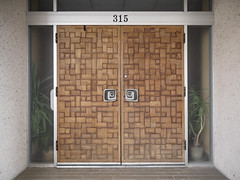 Stylized grids of varyingly opensided wooden rectangles, and showy doorhandles of stylized spirals, at these 1967 doors in the U.S. Sunbelt.