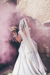 Bride holding a bouquet in wedding dress with pink smoke covering her