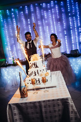 Wedding cake with couple behind it and chapagne in front of it with glasses