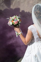 A close up of a bride's hand and her bouquet with purple smoke