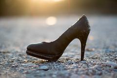 Weggeworfener Stöckelschuh steht stellvertretend für das immer größer werdene Problem von Modemüll