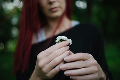 A woman red hair holding small daisies