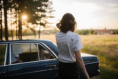 A picture of a Girl from behind in a forest with sunset in the background and a car.