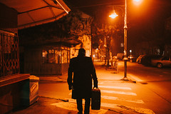A man walking in the street in the night holding a suitcase