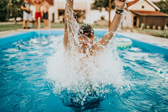 A guy coming out of water with his hands raised in the air out of a pool