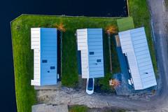 Drei Häuser am Wasser aus der Luft fotografiert in Akmarijp, Niederlande