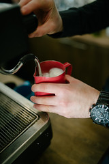 cooking milk on an espresso machine, hands and watch showing