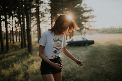 A picture of a girl from the front in a forest with sunset in the background and a car.