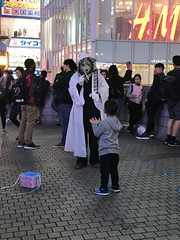 A street performer dressed in a dog suit entertains the kids and looks for handouts near the Dotonbori canal