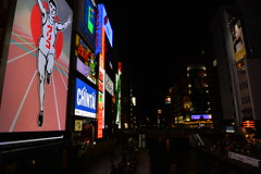 Looking down the Dotonbori canal beside the Glico running man sign