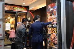 Businessmen in suits look at some of the food menus in Namba- Dotonbori