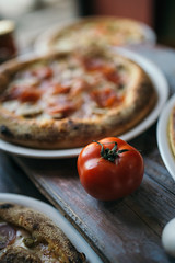 Close-up of a fresh tomato next to a pizza in a restaurant