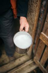 A farmer holding a bowl of fresh goat milk