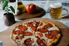 Pizza served on a wooden plate with beer and tomator in the background
