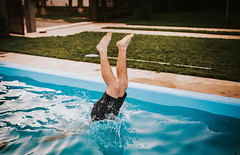 Shoot of a pool with a person going diving in the water with legs up with grass in the background