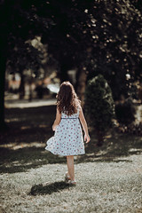 A girl in a white dress with spots outdoors in  front of a park