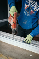 Handyman working with protective gloves and electric drill, drilling a window frame