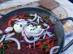 Shakshuka: a steaming hot North African casserole with tomatoes, fresh peppers, red onions, two eggs and toasted bread