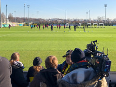Mann mit Videokamera und Fussballfans am Rande des BVB-Trainingsplatzes