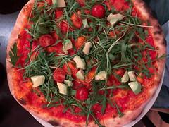 Aufnahme von oben: vegane Pizza ohne Käse und mit Tomatensauce, Avocado, Rucola und Cherrytomaten