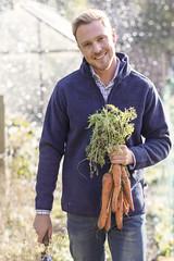 Man wearing fleece jumper holding a bunch of carrots
